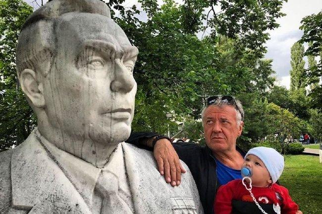 Артур Ваха с ребенком рядом со статуей Брежнева
